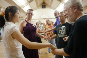 SU student Xiaoli Zhou, Carly Dwyer, Eric Pinney and Stephen Ammholtz join hands four for a dance.